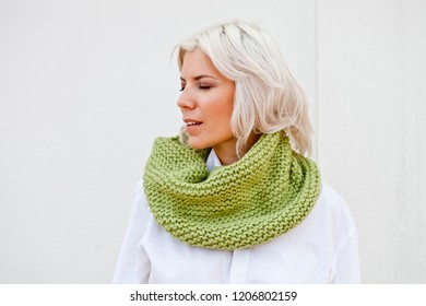 Pretty young woman in warm green wool knitted snood scarf.