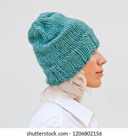 Pretty young woman in warm turquoise beanie wool knitted hat.