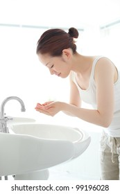 Pretty young woman washing her face at a wash basin
