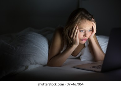 Pretty young woman watching something awful/sad on her laptop in bed at night in a dark bedroom (shallow DOF; color toned image)