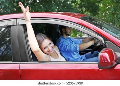 Pretty young woman waving through open car window