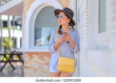Pretty young woman with wear hat and sunglasses fashion chatting on the smart-phone at the city street background. pretty girl having smart phone conversation in sun light.