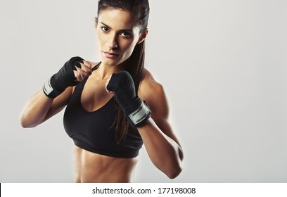 Pretty young woman wearing boxing gloves posing in combat stance looking at camera. Fit young female boxer ready for fight on grey background