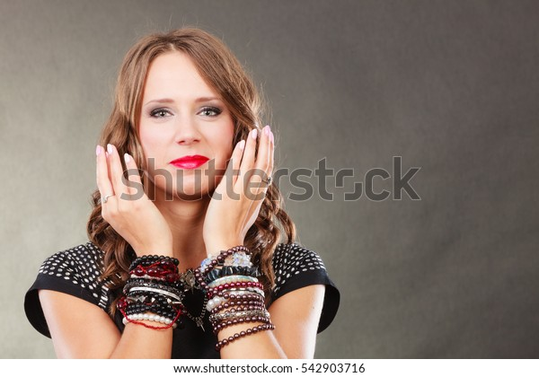 Pretty young woman wearing multiple bracelets jewellery necklace in black elegant evening dress on gray