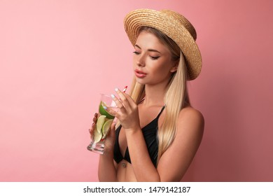 Pretty young woman wearing stylish bikini with cocktail on pink background