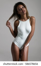 Pretty young woman wearing white body looking at camera and touching her hair.