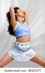 Pretty young woman in white mini skirt and blue top isolated on light gray background