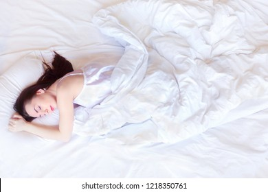 Pretty young woman in white silk underwear sleeps at big white bed, top view