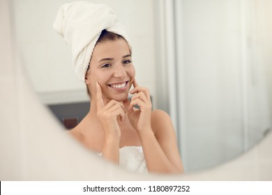 Pretty young woman in white towels in a bathroom giving the camera a lovely friendly smile as she applies cream to her cheeks while bathing in a skin care and hygiene concept