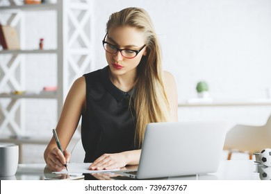 Pretty young woman working on project at modern office desk with laptop, coffee cup and other items. Job concept