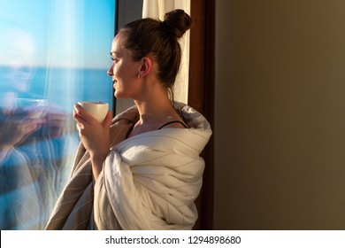 Pretty young woman wrapped in a blanket is standing near window and enjoying first morning coffee on sunshine. An early waking and the beginning of a new day. Copy space