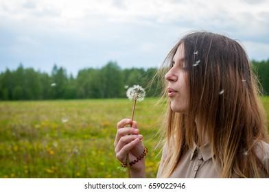 Pretty young women blowing to dandelion in field
