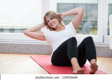 Pretty young women performs fitness exercises at home