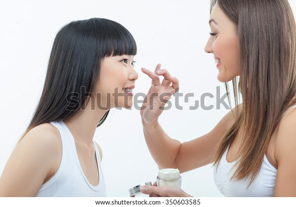 Pretty young women are standing and smiling. The Caucasian girl is applying cream on face of her asian friend. Isolated on background