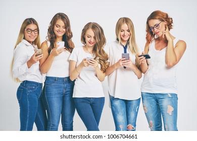 Pretty young women using smartphones. Group studio portrait.