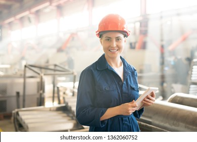 Pretty young worker of factory in helmet and blue workwear surfing in the net whiole looking for online information