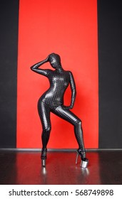 Pretty Zentai Catsuit Theatre Actress Acting Girl Posing In Latex Rubber PVC Vinyl Carbon Clothes High Fashion Vogue Style Red Background Isolated