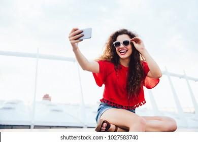 Prettygirl with curly hair takes a selfie on telephone, cheerfully smiling, sitting on marble slab outdoors. Dressed in stylish clothes, in sunglasses.