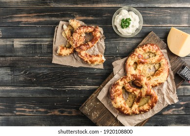 Pretzel with cheese on a wooden board on a dark background. Appetizer for beer. Top view with a copy space for the text. Horizontal orientation.