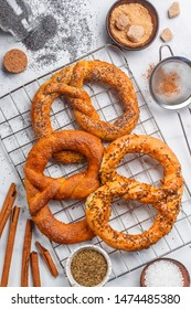 Pretzel. Freshly baked pretzels with sugar, poppy seeds, cinnamon and cumin. Delicious homemade sweet and salty pastries and ingredients on the table. Selective focus, top view