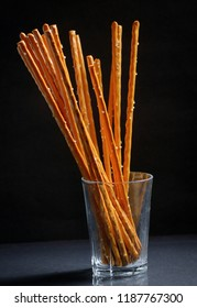 Pretzel sticks in small glass on black background