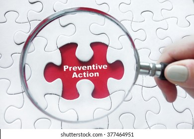 Preventive Action word with hand holding magnifying glass over jigsaw puzzle