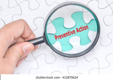Preventive Action word with hand holding magnifying glass over jigsaw puzzle. Selective focus.