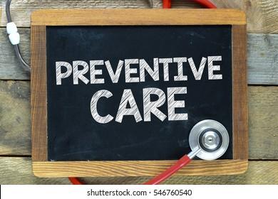 Preventive care / Preventive care inscription in chalk on a blackboard, a stethoscope and a wooden background
