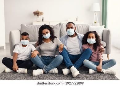 Konzept der Präventivmaßnahmen. Portrait der jungen afrikanischen amerikanischen Familie von vier Menschen, die während der Selbstisolierung Einwegmasken tragen, Eltern und Kinder zu Hause bleiben, auf dem Teppich sitzen