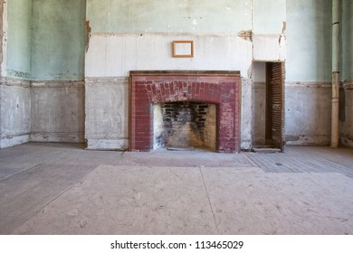 A previously formal room with fireplace and blank picture over the mantal, in an old long abandoned large house.  Looks to be in dire need of repair.