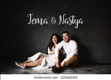Pre-wedding photo shooting. Happy and smiling newlyweds sit on the floor before the black wall