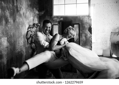 Pre-wedding photoshooting. Hipster blonde bride and groom have fun posing in the loft