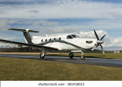 Pribram, CZECH REPUBLIC - 24th February 2016. Single turboprop aircraft PILATUS PC-12 NG white modern design with stripes, parked on runway with clouds.