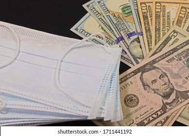 Price gouging during shortage of virus masks.  Europe and global pandemic. Pile of anti virus surgical face masks and money. surgical mask with covid-19 word.Concept.