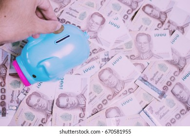 The price of one thousand baht banknotes with hand and piggy bank on a white background.Vintage filter effect