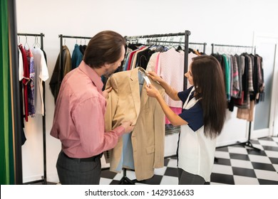 A price tag. Beautiful alluring dark-haired appealing stylish good-looking mature spouses looking at the price-tag of the blazer.