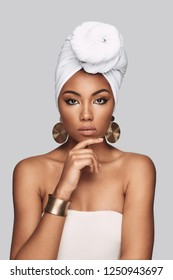 Pride. Attractive young African woman in turban keeping hand on chin while standing against grey background