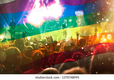Pride community at a parade with hands raised and the LGBT flag - symbol of love and tolerance