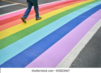 Pride Crosswalk, Vancouver. A pedestrian using the rainbow colored crosswalk in downtown Vancouver.