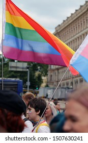 Pride parade of Helsinki, Finland, June 2019. People marching for equality, acceptance and LGBT community rights. In this photo you see two big colorful flags and cloudy sky and buildings. Color image