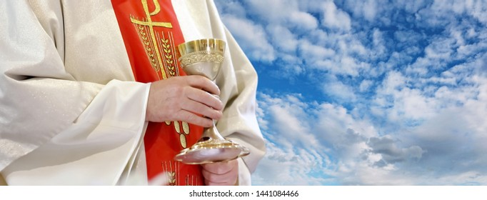 Priest with chalice celebrate mass and empty place for text against blue heaven