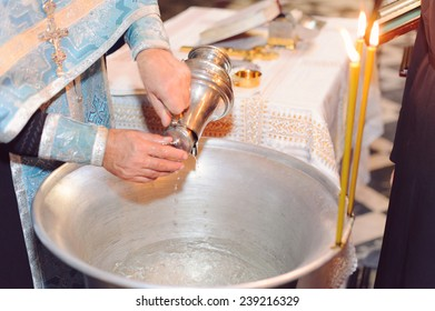 priest filling metal bowl with water