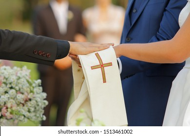 Priest giving blessing with his hand to a couple getting married. Happily ever after concept. Engagement couple holding hands at a wedding ceremony. Outdoor marriage close up.