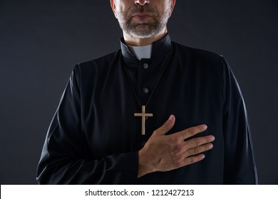 Priest hand in heart gesture with cross on black background