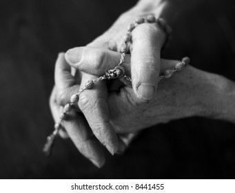 Priest hand holding rosary over black, dramatic look isolated on black