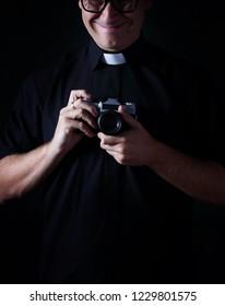 Priest hold a photo camera