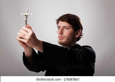 Priest holding a golden crucifix with respect