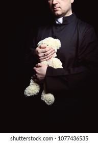 priest holding a teddy bear
