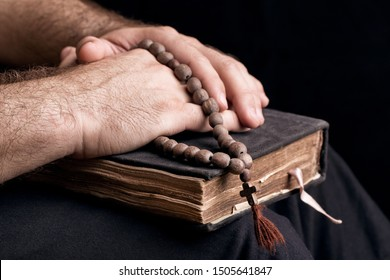Priest and old bible book. Priest hands lying on an old bible. Rosary, bible and priest close-up.