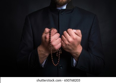 Priest on a dark background. Close-up